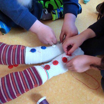 Couture de boutons sur les pieds de la mascotte